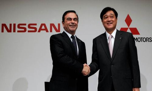 Nissan Motor's CEO Carlos Ghosn shakes hands with Mitsubishi Motors Corp.'s President Osamu Masuko at the end of a joint news conference in Tokyo